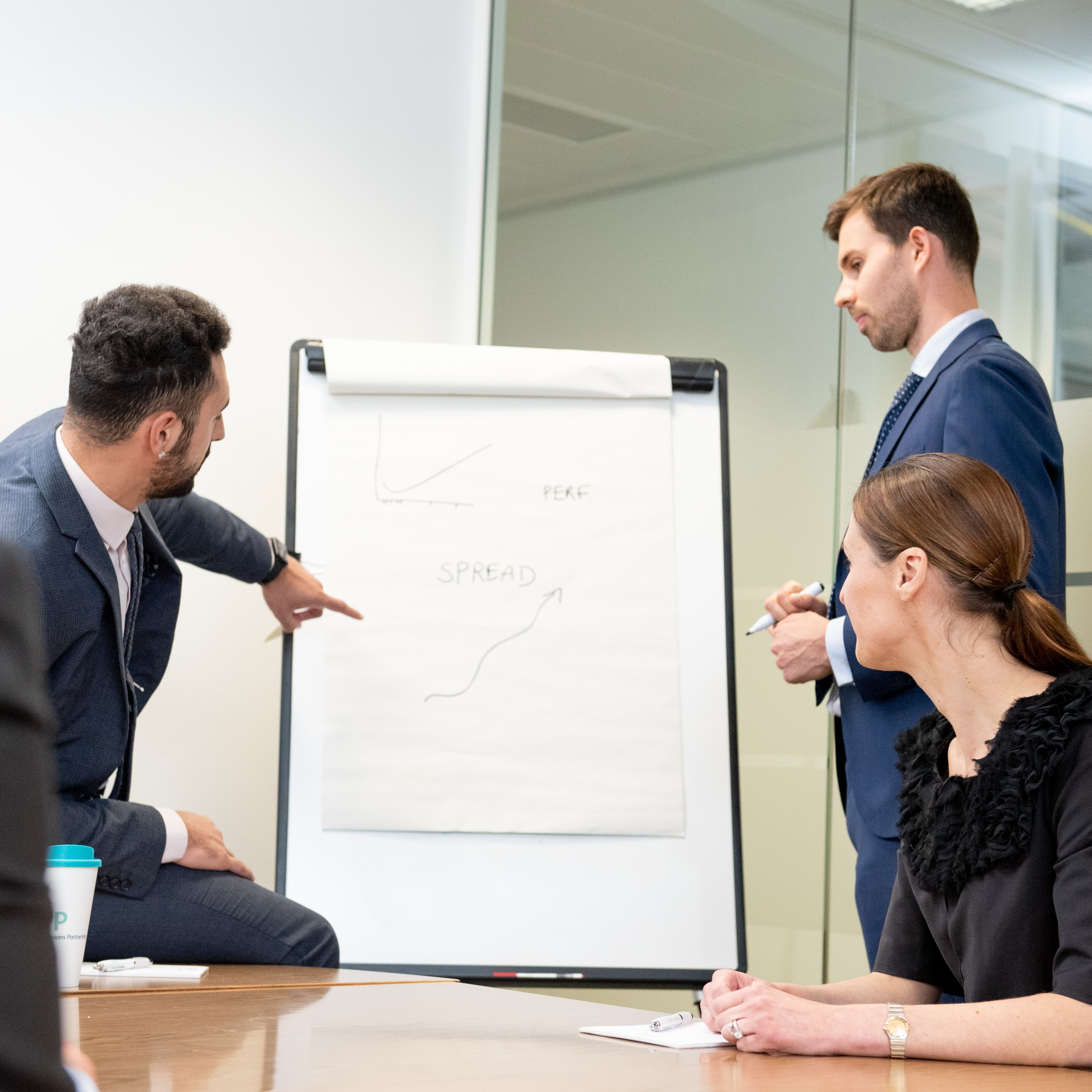 Three people in a meeting looking at a flip chart