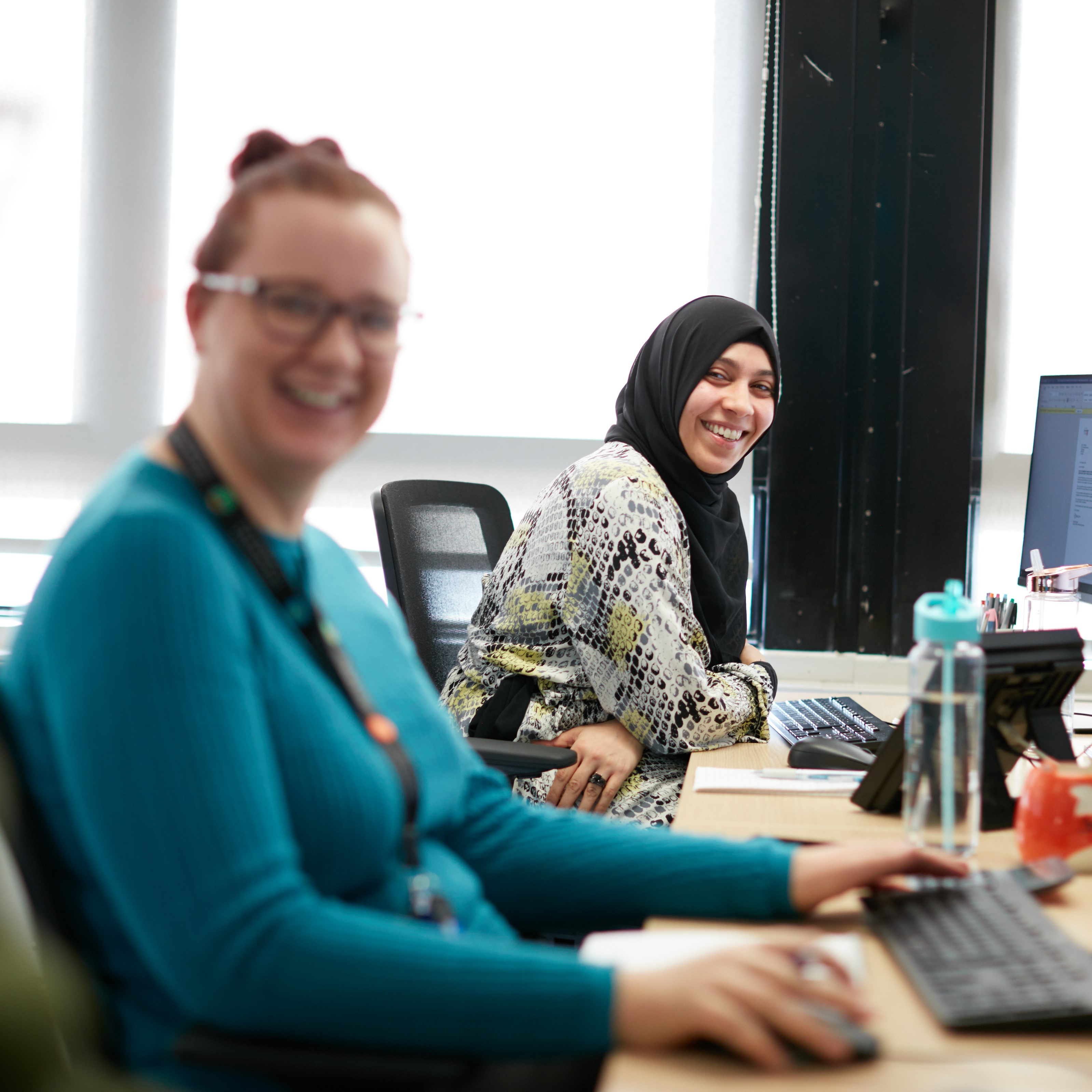 Two LPP female colleagues sit alongside each other at their desks. They are smiling and looking towards the camera.